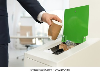 Man putting used paper cup into trash bin in office, closeup. Waste recycling