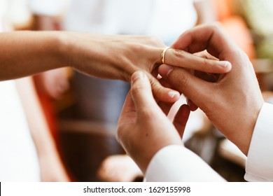 Man putting wedding ring on woman finger. Exchange Wedding rings. happy groom and bride. Wedding day concept.