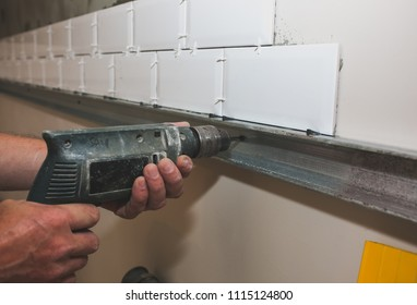 Man is putting white tiles on the grey concrete. Maintenance repair works renovation in the flat. Restoration indoors. Man is working with a drill.
