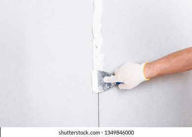 Man with putty knife shows how to hide the connection place between two pieces of dry walls using putty and construction tape