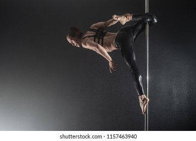 Man with pylon. Male pole dancer dancing on a black background. Strong and graceful Guy dancing in smoke