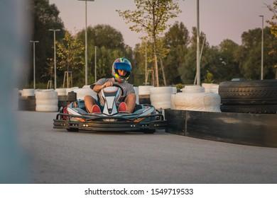 Man is racing in commercial amateur gokart race on a closed circuit. Fun leisure racing activity, go kart trophy between friends.
