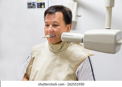 Man with radiation protection vest receiving dental  X-Ray at a dentist