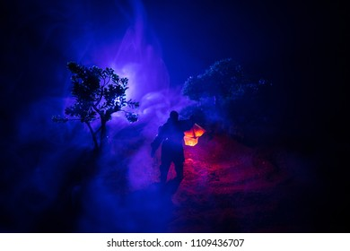 Man in raincoat coming from dark forest with glowing lantern in his hand concept. Silhouette of a horror killer with lamp. Decoration