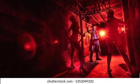 Man in the raincoat is shooting walking zombie women.