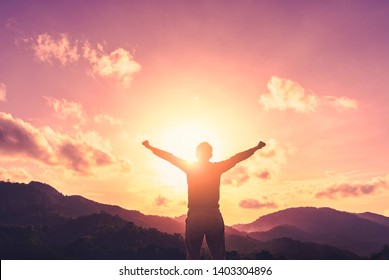 Man raise hand up on top of mountain and sunset sky abstract background. Copy space of freedom feel good and travel adventure holiday concept. Vintage tone filter effect color style.