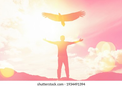 Man raise hand up on top of mountain and sunset sky with eagle birds fly abstract background. Copy space freedom travel adventure and business victory concept. Vintage tone filter effect color style.