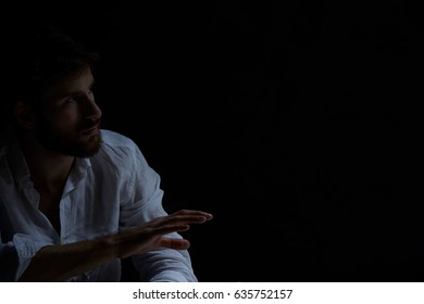 Man with raised hand sitting alone in the darkness