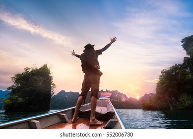 Man raised hands enjoying to adventure trip of a lifetime floating in a boat on the asia lake with sunset among the islands with mountains