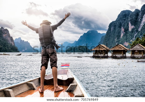 Man raised hands enjoying to adventure trip of a lifetime floating in a boat on the Asia lake with houseboat at lake river in natural attractions and mountains