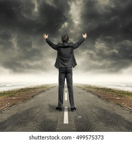 Man with raised hands on asphalt countryside road. and dark stormy sky on the horizon.