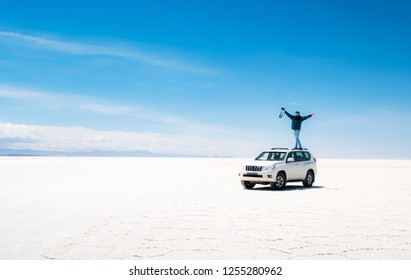 Man with raised hands standing on car in spacious sunshine Salar de Uyuni