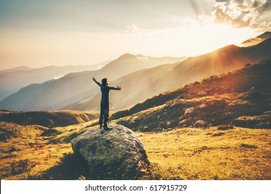 Man raised hands at sunset mountains Travel Lifestyle success and wellness emotional concept adventure vacations outdoor hiking harmony with nature aerial view.