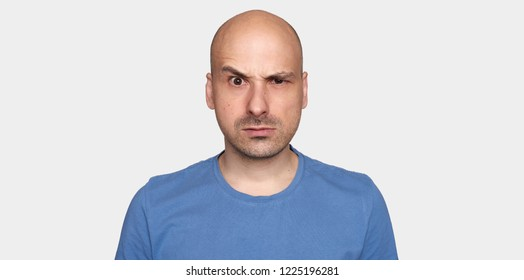 man raised his eyebrow. Angry bald guy in blue t-shirt. Isolated on grey background
