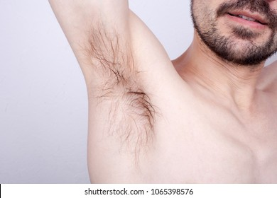 The man raised his hand up, and shows unshaven armpit. Unpleasant smell.