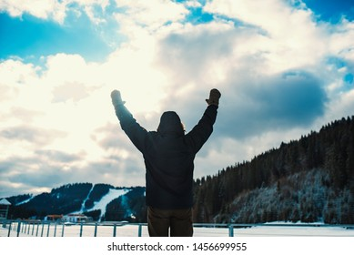 Man raised his hands up near frosen lake in mountains  back view
