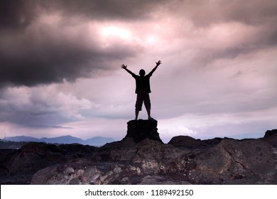 a man raises his hands up on the rock in cloudy sky