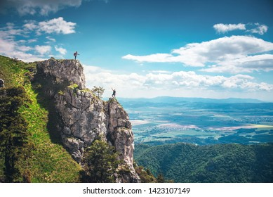 Man raising hand to woman at the top of the rock, trust and help in partnership, concept photo. Hiking and adventure in Two, love, marriage, valentine postcard.