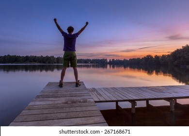 Man raising his arms while enjoying the sunset as a concept for a happy achievement
