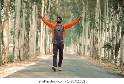 Man raising two hands walking in an empty road unique photo