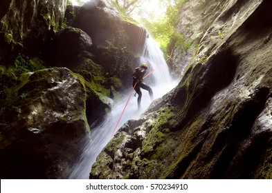 man rappelling down a waterfall backlit