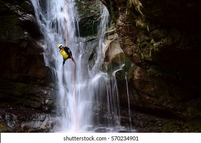 man rappelling down a waterfall with yellow backpack