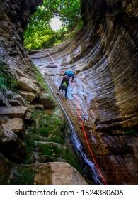 Man rappelling a waterfall canyon