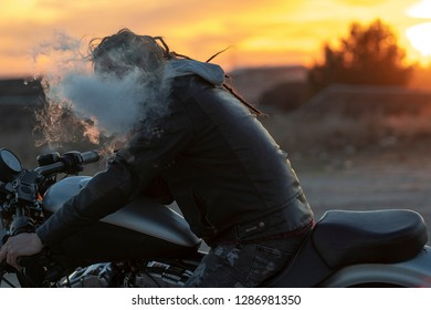 man rastafarian driving motorbike on the sunset