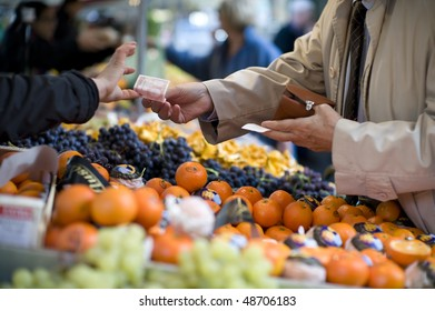 A man reaches across a row of fruit in an outdoor market to pay a vendor with a 10 Euro bill. Focus is tight on the bill changing changing hands. The foreground and background are out of focus.