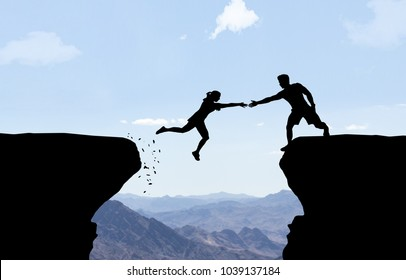 Man reaching hand to woman jumping over abyss.
