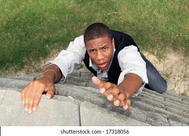 Man reaching for help while climbing a wall