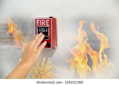 Man is reaching his hand to push fire alarm hand station. Hand of man pulling fire alarm switch on the white wall as background for emergency case at the new factory building.