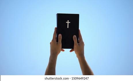 Man reaching out hands to sky holding bible, new testament, ten commandments