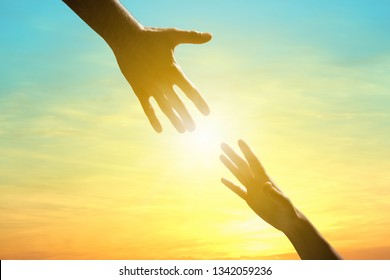 Man reaching for woman's hand at sunrise outdoors, closeup. Help concept