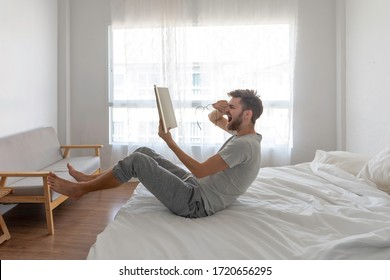man read book on  bed. He enjoys it, He laughed until the tears flowed.