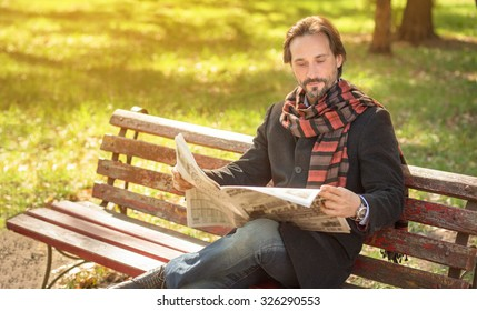 Man reading about the current events in the newpaper in the park. Handsome man resting on the bench in autumn season.
