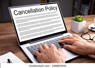 Man Reading Agreement Of Cancellation Policy On Laptop Screen Over Wooden Desk At Office
