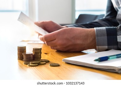 Man reading bank statement, check reminder, tax refund document, phone bill, or financial letter. Home or health insurance price and cost concept. Person holding paper invoice in hand.