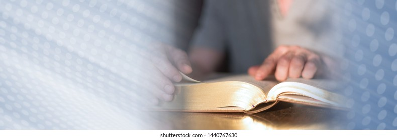 Man reading the bible in dim light; panoramic banner