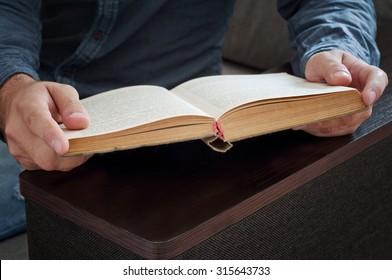man reading a book closeup. Top view