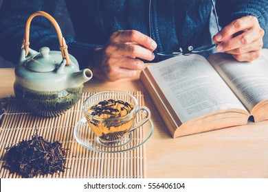 A man reading a book with cup of tea and tea pot