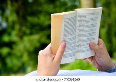 man reading book in garden