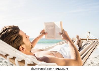 Man reading book in hammock on the beach
