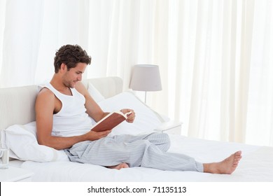 Man reading a book on his bed at home