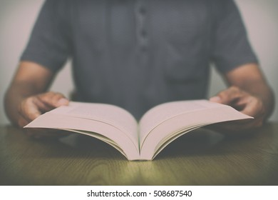 A man reading a book on wooden table with vintage filter blurred background