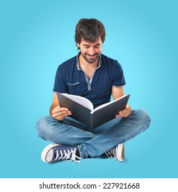Man reading a book over blue background