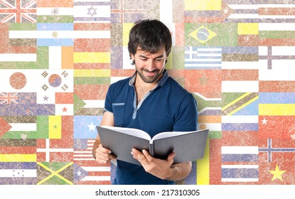 Man reading a book over flags background