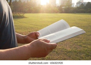 A man reading a book in a park