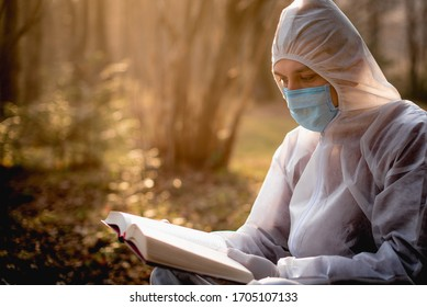 man reading a book in protective cloths, in background trees,park