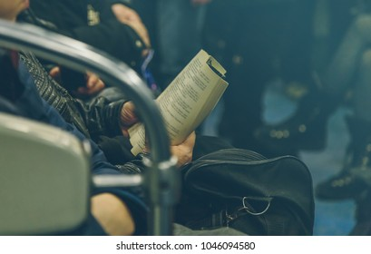 a man reading a book in a subway train in Russia close-up